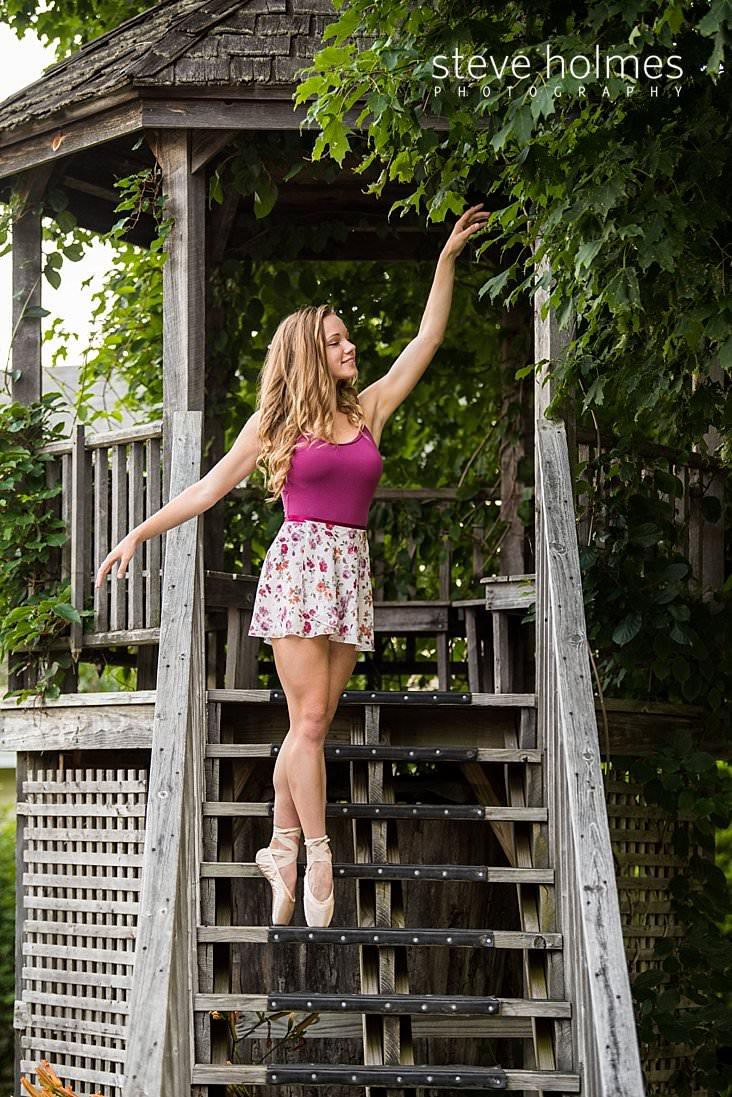 09_Young woman stands on her toes in ballet shoes with arms outstretched on stairs to pergola.jpg