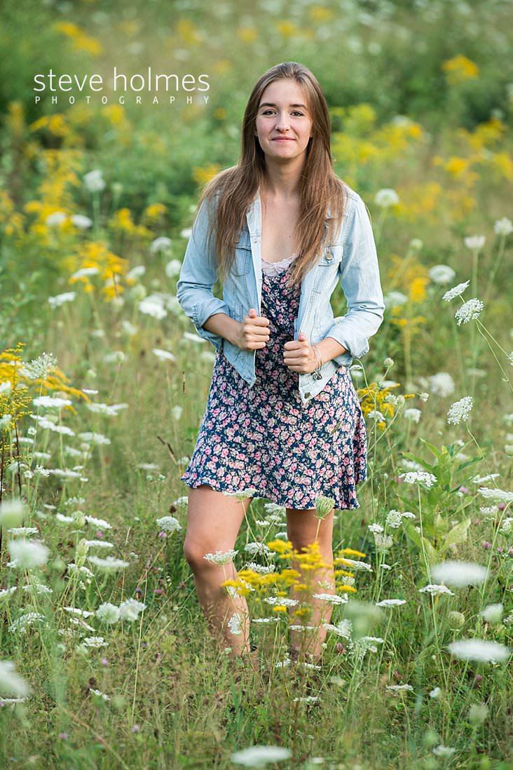 10_Senior photo of teen girl walking through field of flowers wearing floral dress and jean jacket.jpg