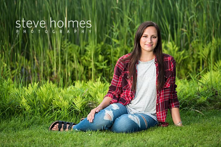 10_Teen in red flannel and jeans sits on the grass in front of a pond for senior portrait.jpg