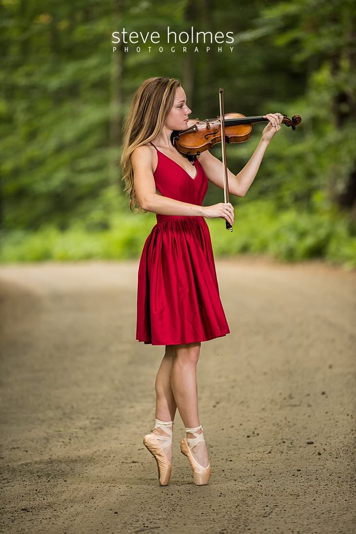 11_Teen girl wearing red dress stands on her toes in ballet shoes and plays violin on country road.jpg