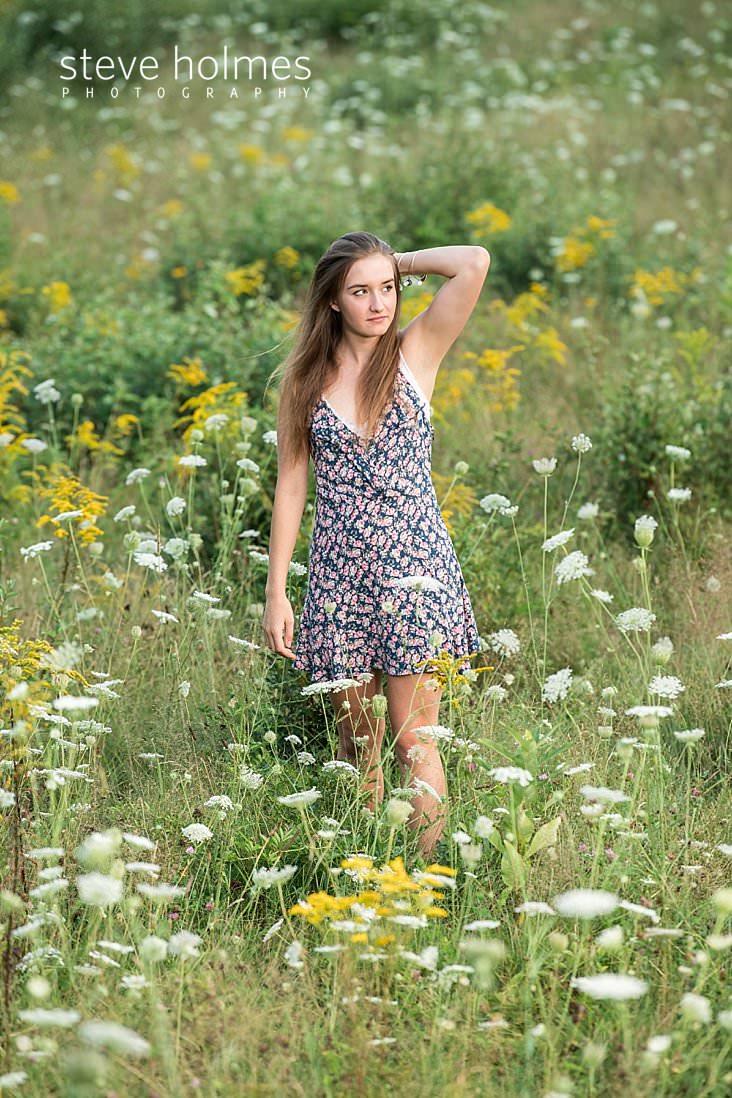 11_Teenaged girl brushes back hair as she walks through field of flowers for senior photo.jpg
