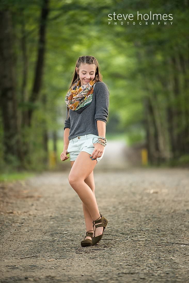 12_Young girl in grey sweater and shorts walks down country road.jpg