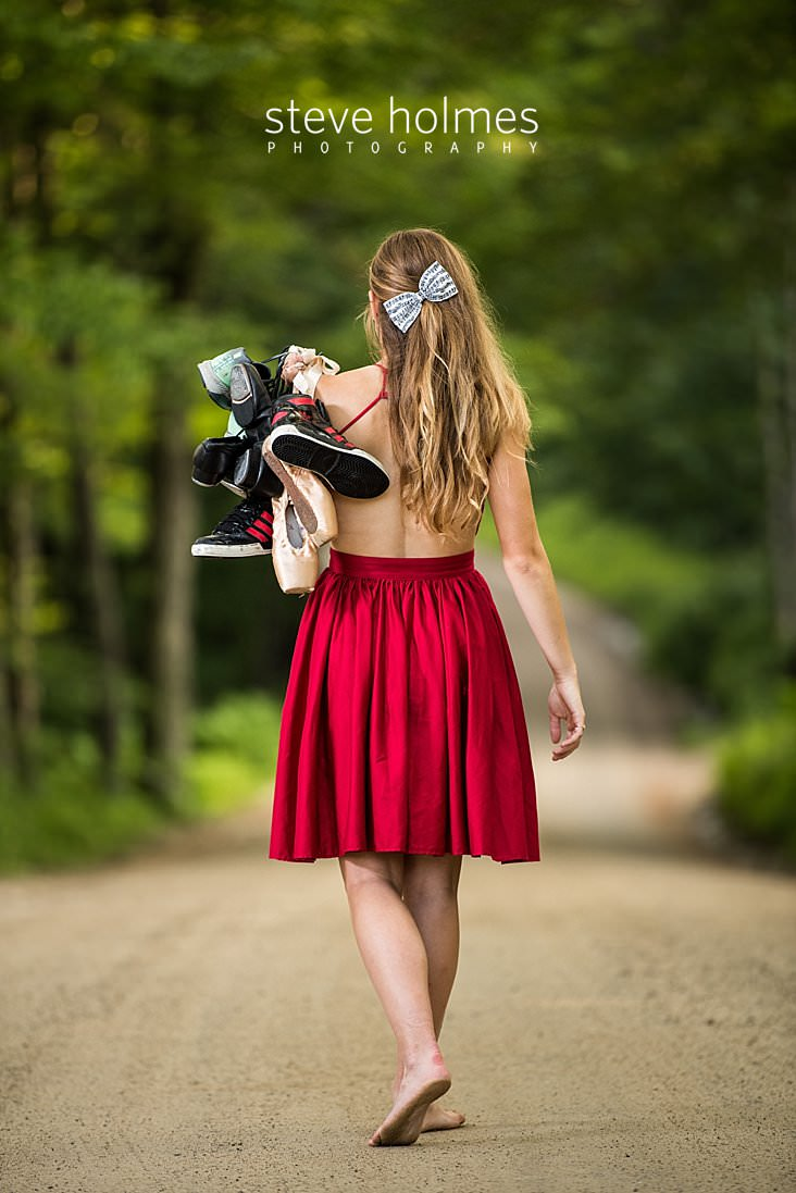 13_Teen girl wearing red dress walks down country road barefoot with her collection of dance and running shoes.jpg