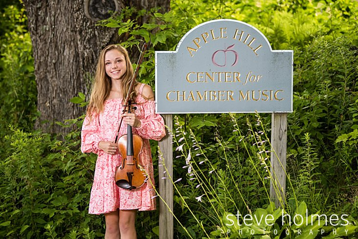 14_Young woman in pink off the shoulder floral dress poses with her violin next to a sign that reads Apple Hill Center for Chamber Music.jpg