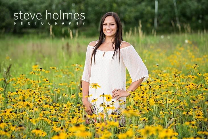 18_Teen girl in white shift dress poses for senior portrait with hand on hip in field of flowers.jpg