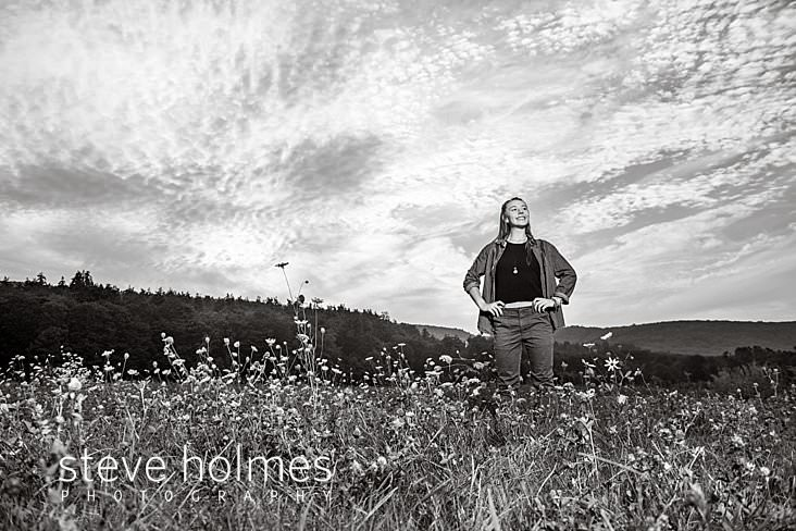 19_Black and white landscape portrait of a teen girl with hands on her hips smiling into the distance.jpg
