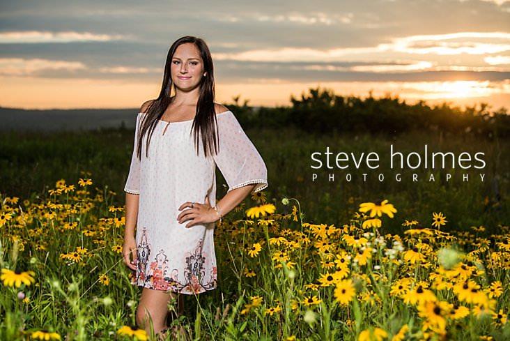 20_Senior portrait of teen girl wearing white shift dress in field of flowers at sunset.jpg