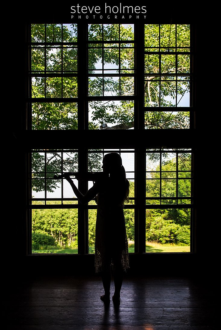 21_Silhouette of teen girl playing violin in font of large wall of windows and green landscape.jpg