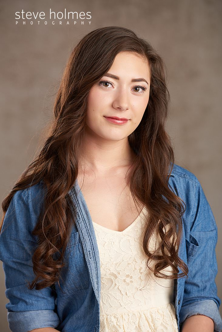 01_Young woman with brown, wavy hair looks at camera for studio senior portrait.jpg