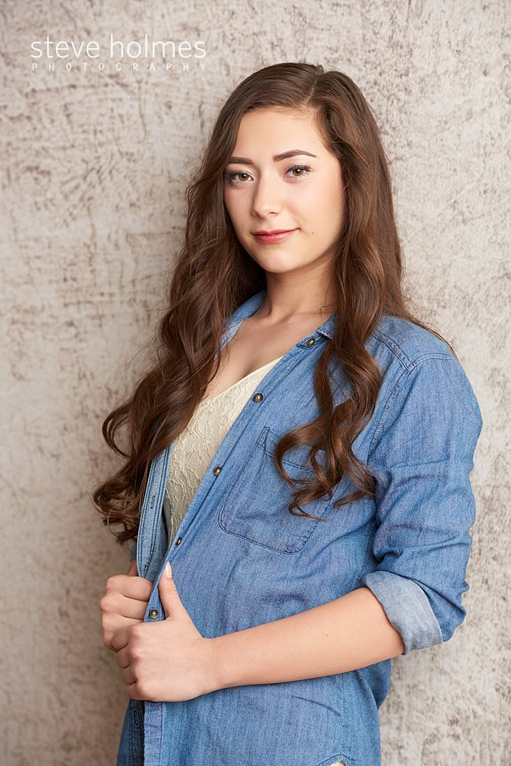 02_Teen girl wearing jean top looks at camera for studio senior portrait.jpg