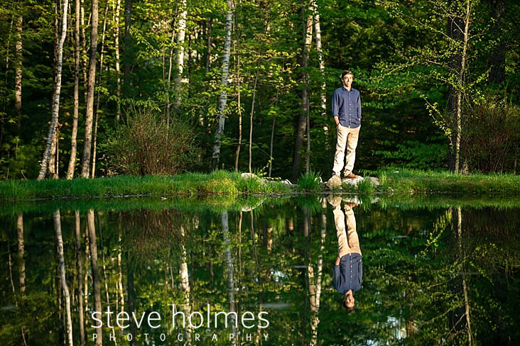 02_Teenaged boy is reflected in the pond he stands next to for senior portrait.jpg