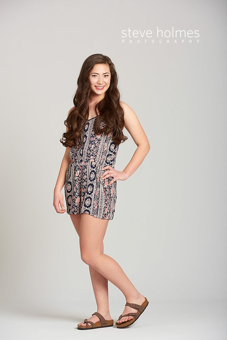 03_Brunette teen in patterned jumper stands with her hand on her hip in studio senior portrait.jpg