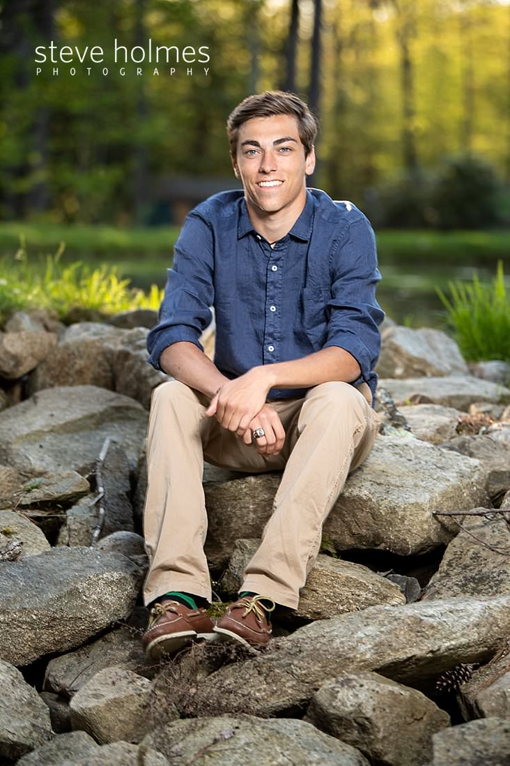 03_Teen boy in blue shirt and khakis sits on a pile of stones for senior portrait.jpg