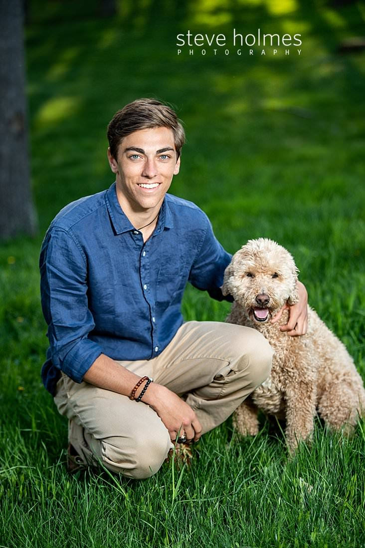04_Teenaged boy in blue shirt and khakis poses with his dog for outdoor senior portrait.jpg