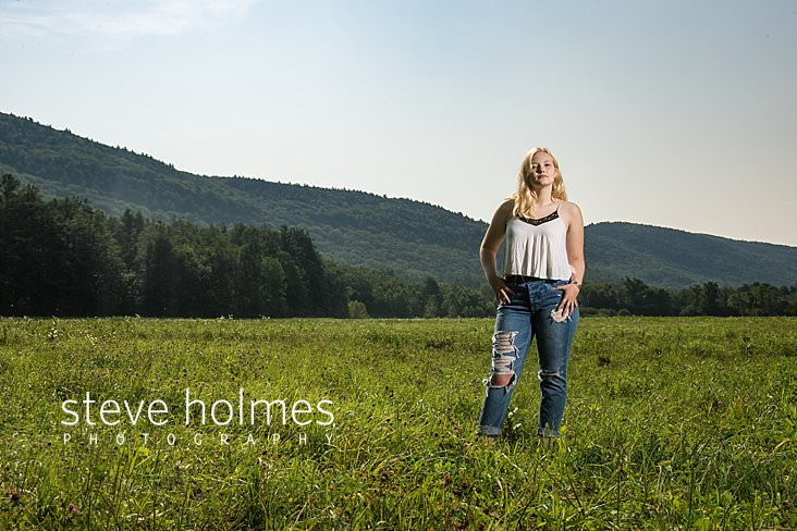 06_Teen in ripped jeans and white tank top poses in summer field with her hands on her hips for outdoor senior photo.jpg