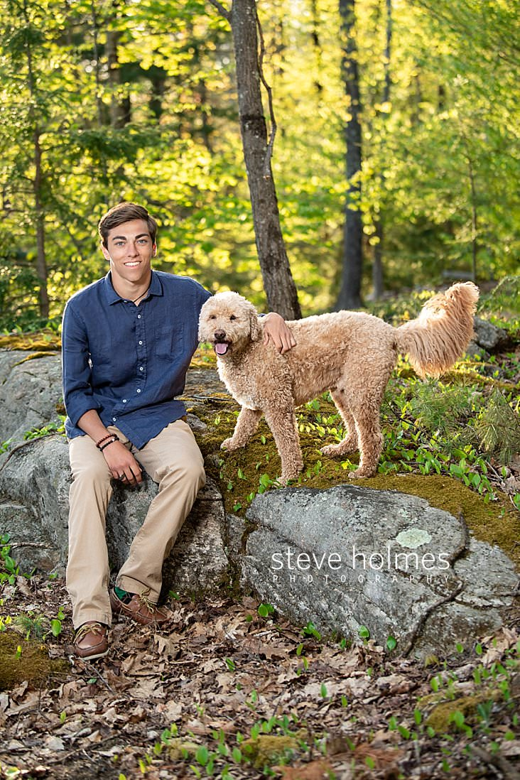 06_Teenaged young man sits in the forest with his dog for senior photo.jpg