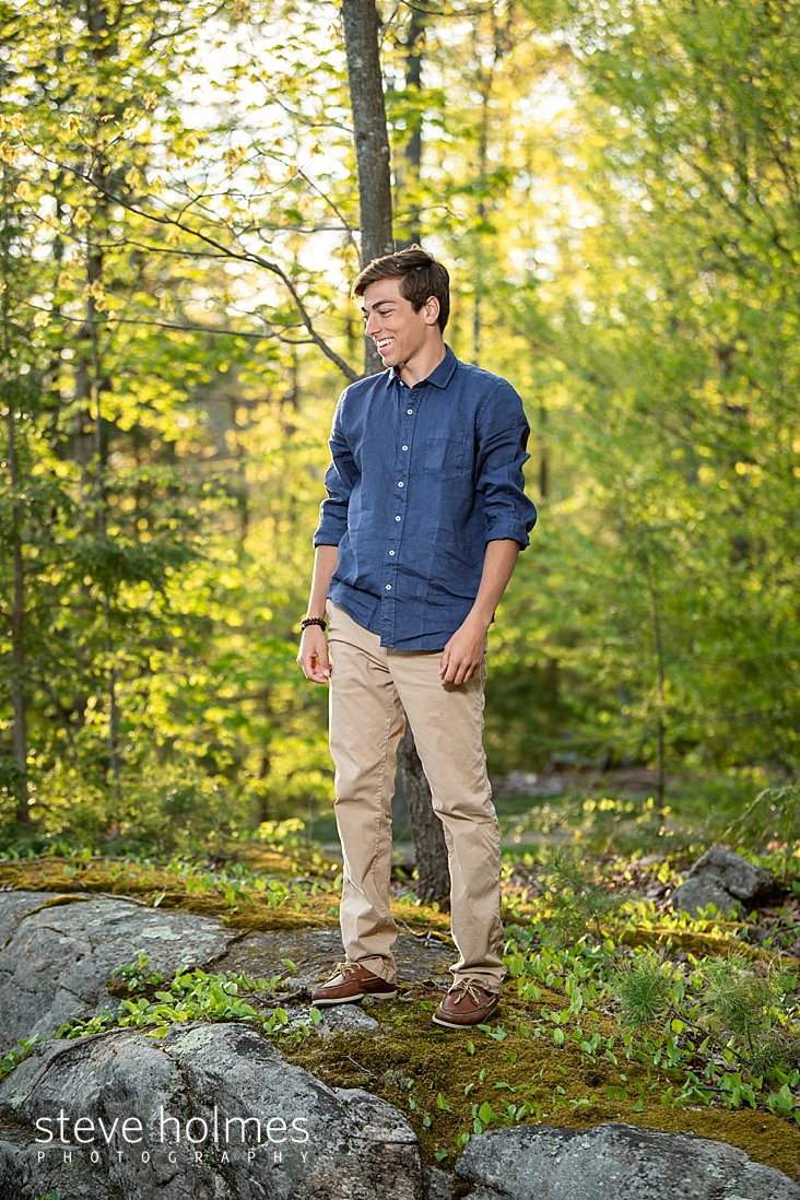 07_Candid senior portrait of a young man smiling in the forest wearing blue button down shirt and khakis.jpg