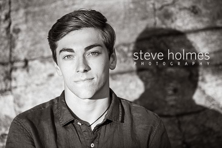 08_Black and white senior portrait of a young man against a stone wall.jpg