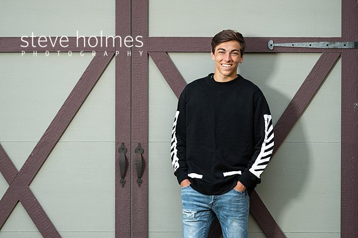 10_Teen boy in black and white sweatshirt and jeans poses in front a barn door for senior photo.jpg