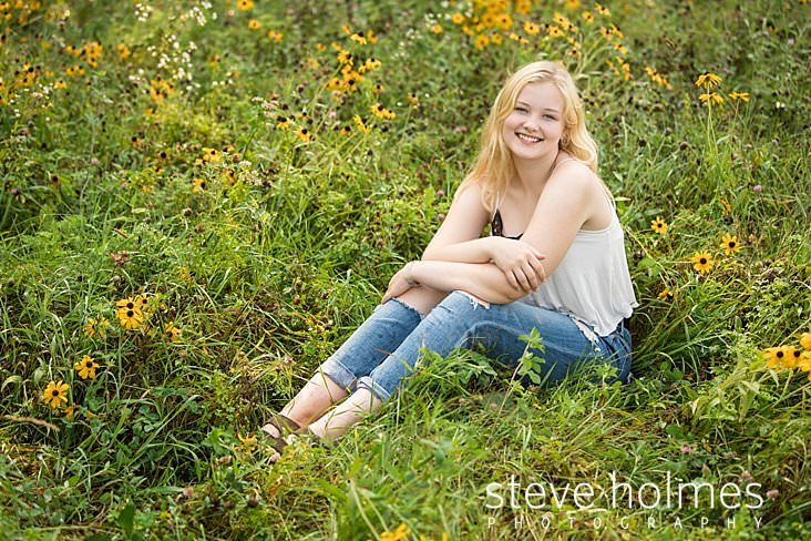 11_Young, blonde woman wearing jeans and a tank top sits in a field of flowers for outdoor senior portrait.jpg