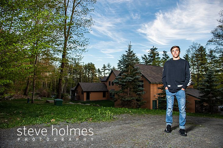 11_Young man stands in front of his house with hands in jean pockets for senior photo.jpg