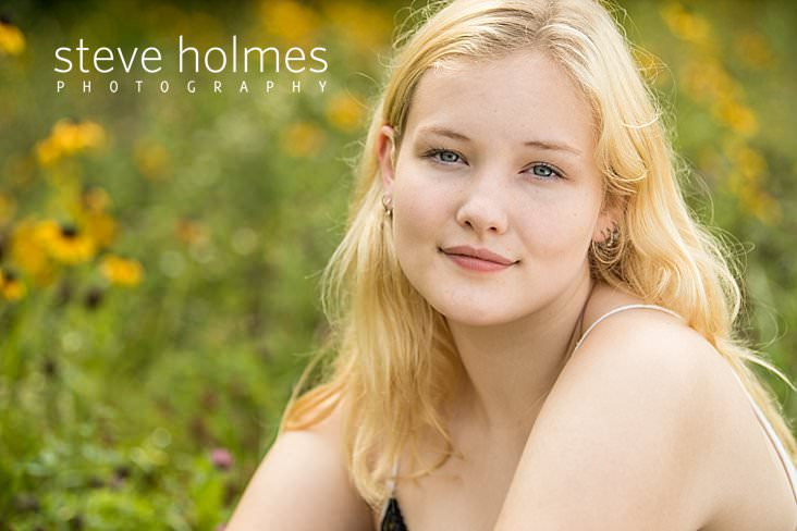 12_Close up senior portrait of young blonde woman with blue eyes in field of flowers.jpg