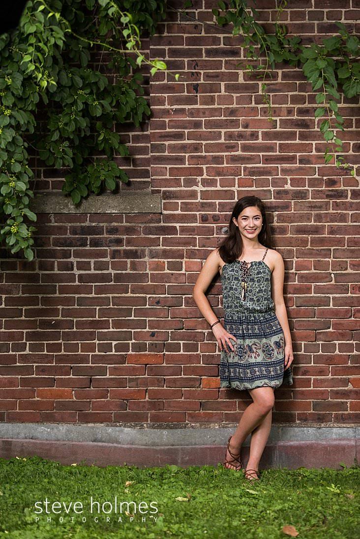 15_Brunette teen wearing Indian patterned dress leans against brick wall for senior portrait.jpg