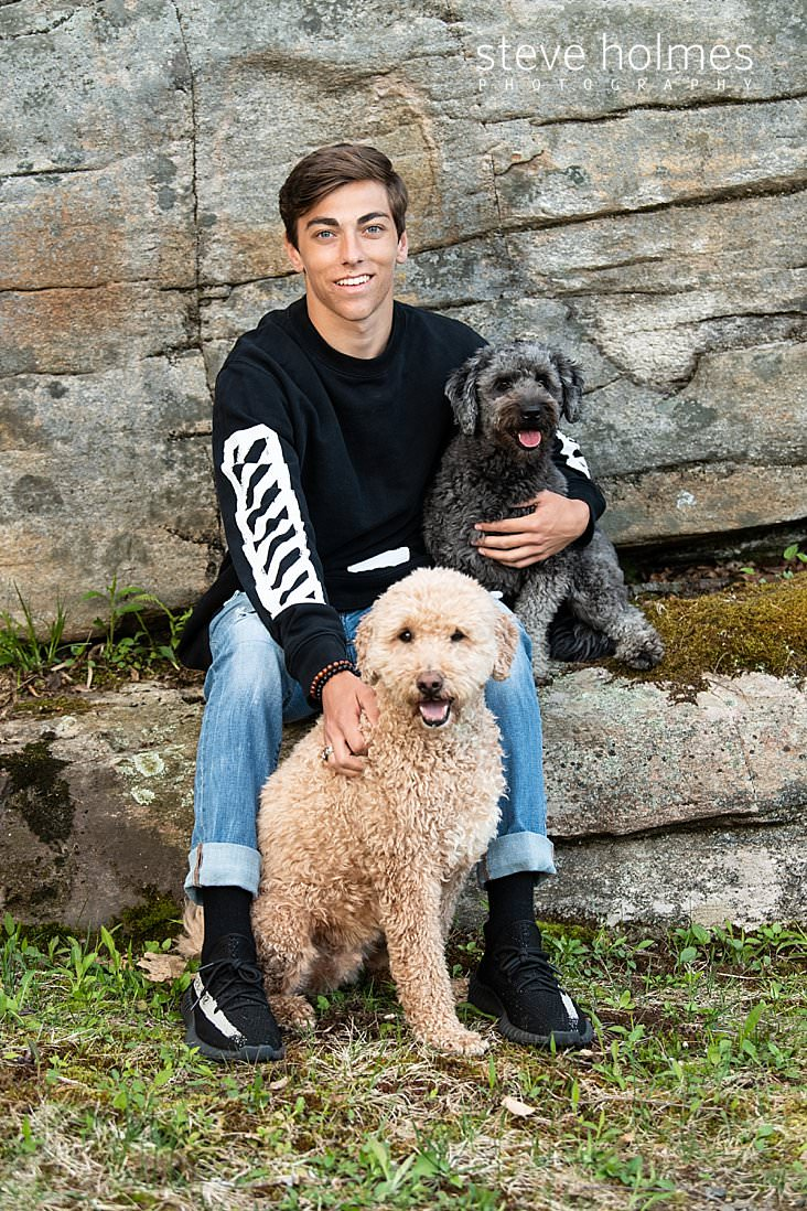 16_Teen boy sits on a stone with his dogs for senior photo.jpg