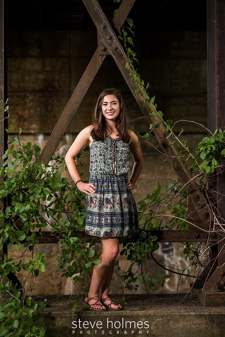 17_Brunette wearing green patterned dress poses under metal structure covered in vines for outdoor senior portrait.jpg