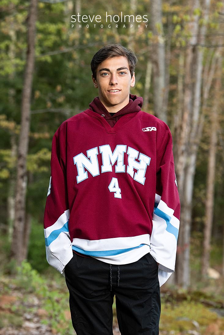 18_Teen boy poses outside in his hockey jersey for senior photo.jpg