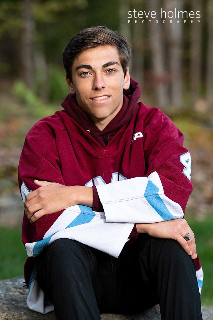 19_Teen boy sits outside wearing his hockey jersey for senior portrait.jpg