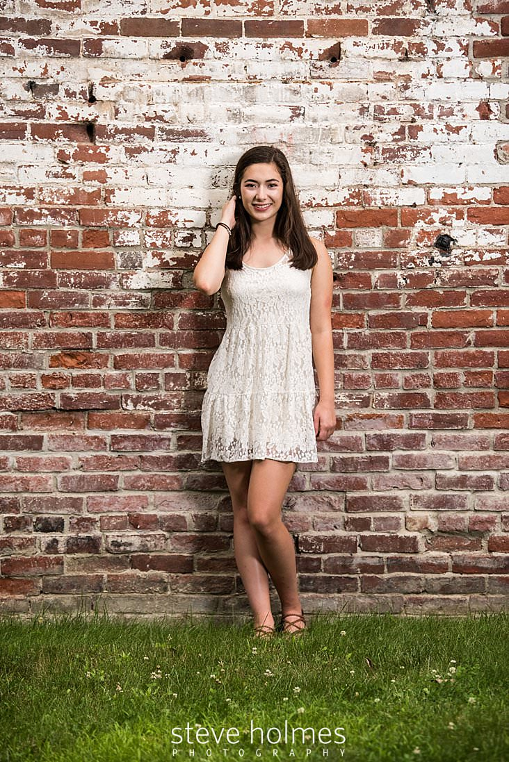 20_Senior portrait of teen in white dress brushing back hair while leaning against a brick wall.jpg