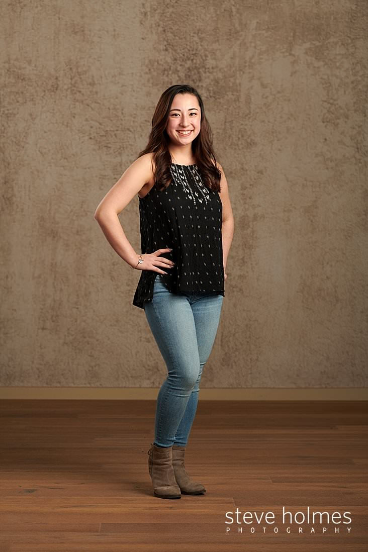 02_Teen girl in jeans and a black patterned tank top stands with her hands on her hips for studio senior portrait.jpg