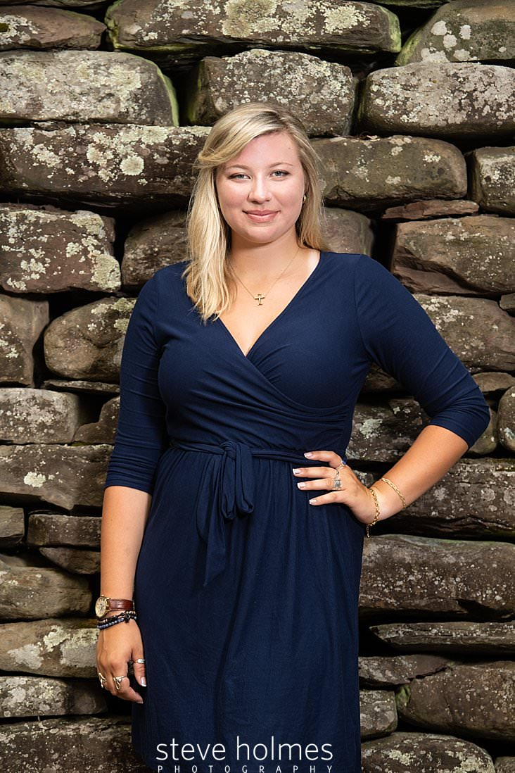 03_Blonde teenaged girl in blue wrap dress poses next to stone wall with hand on hip for outdoor senior photo_.jpg
