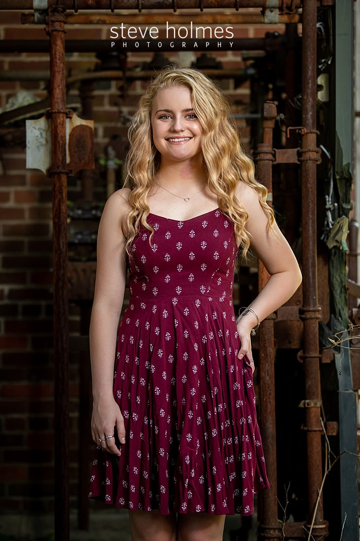 04_Teen in red patterned dress stands with her hand on her hip in front of industrial piping and brick wall for senior portrait.jpg