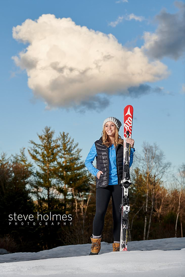 04_Teen stands in the snow with her downhill skis wearing winter boots, leggings, down vest and winter hat.jpg