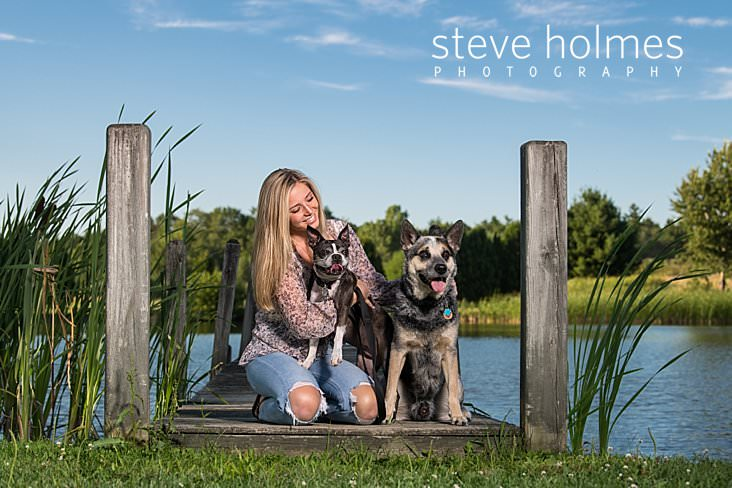 06_Blonde teen kneels on dock in front of pond with her two dogs.jpg