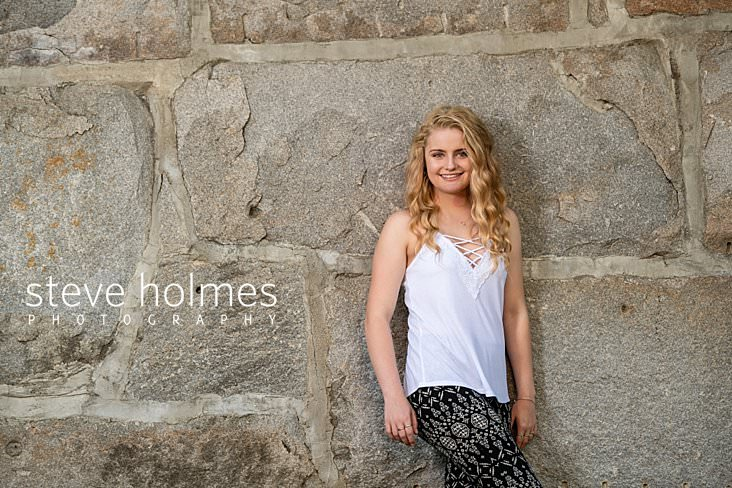 07_Teen in white tank top and black patterned pants leans against stone wall for senior portrait.jpg