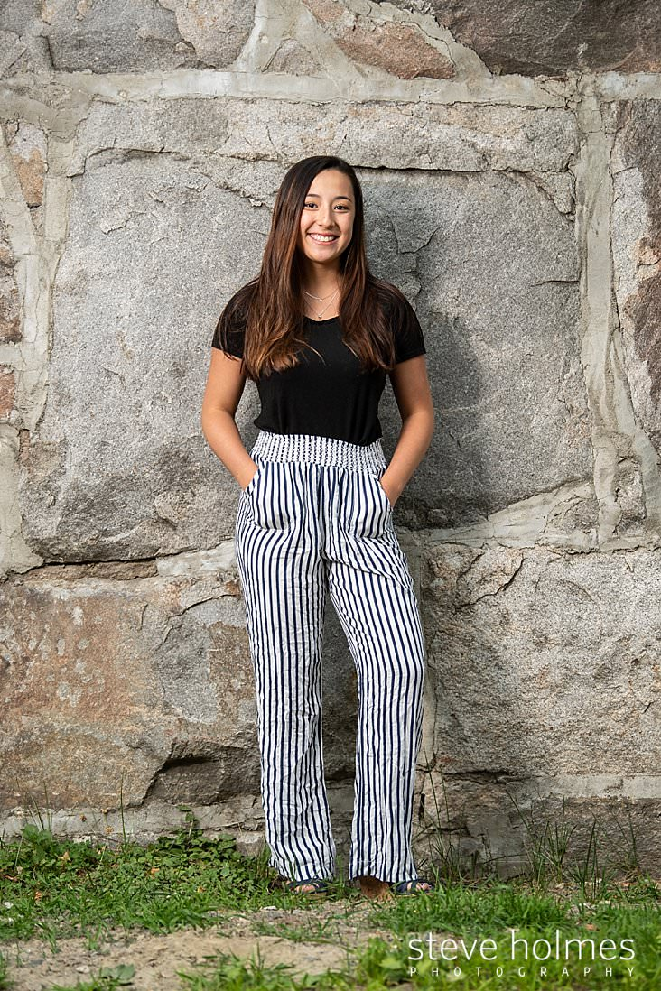 08_Young woman stands against stone wall wearing striped pants and black top for outdoor senior portrait.jpg
