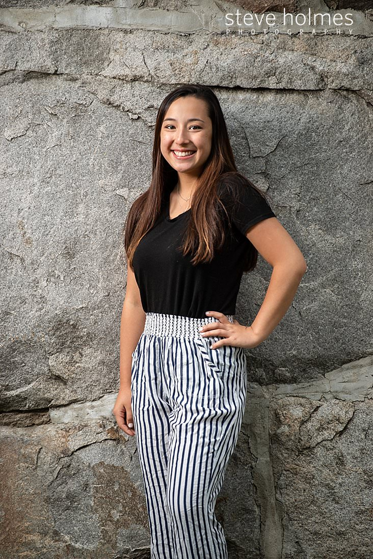 09_Teen stands with her hand on her hip against stone wall for outdoor senior portrait.jpg