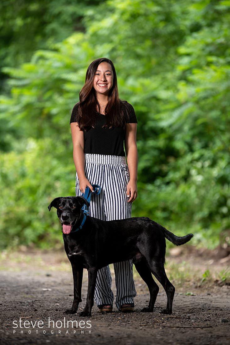 12_Teen girl holds her dog on leash on trail for outdoor senior portrait.jpg
