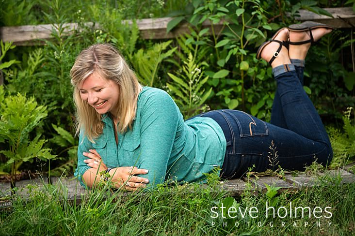17_Blonde teen laughs as she lays in the green foliage of summer for senior portrait.jpg