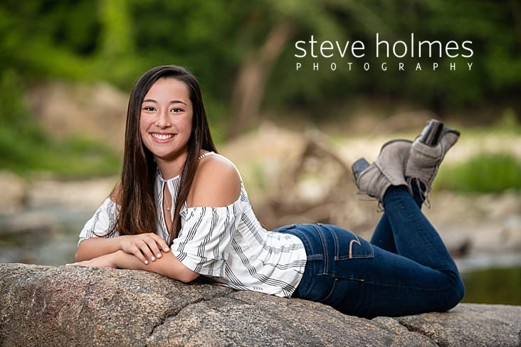17_Teen lays posing on her stomach for outdoor senior photo on rock.jpg