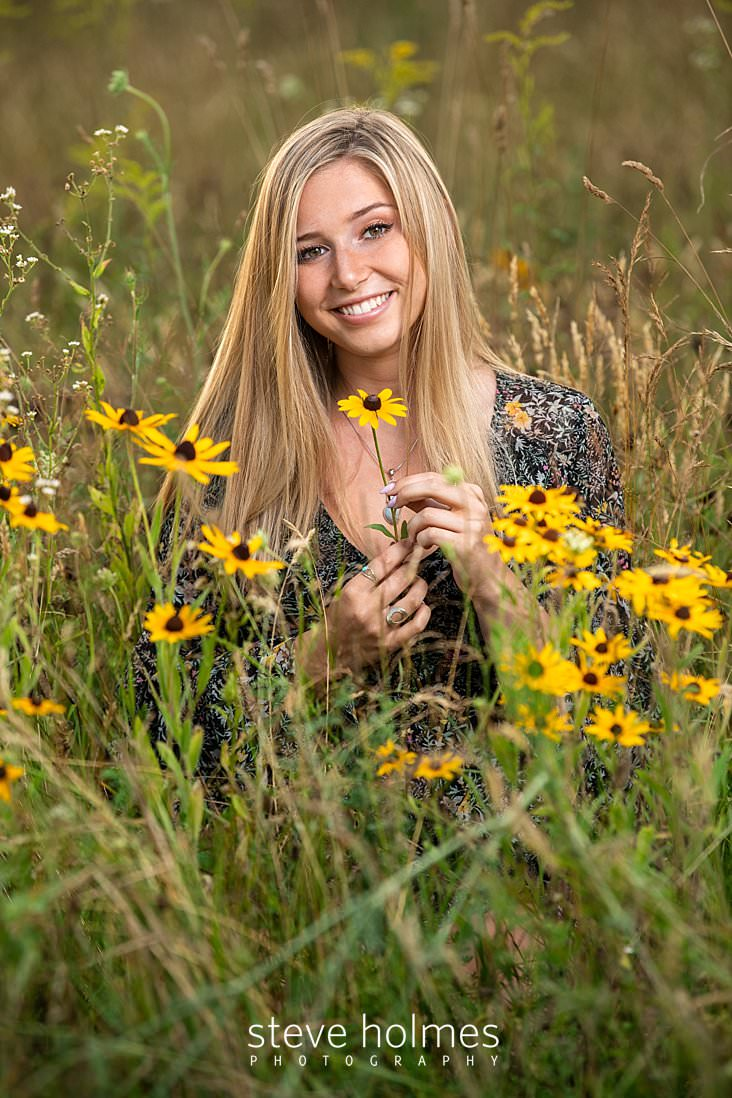 19_Blonde teen sits in field of wildflowers holding a flower she's picked for senior portrait.jpg