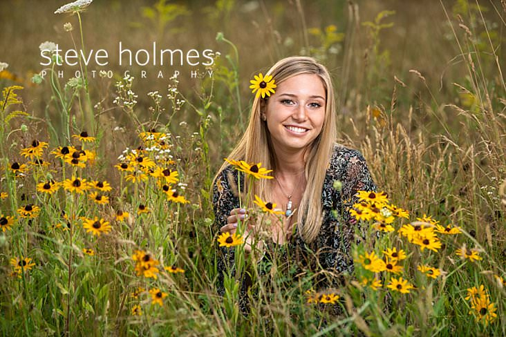 20_Blonde young woman sits in field of wildflowers with a flower behind her ear for senior portrait.jpg
