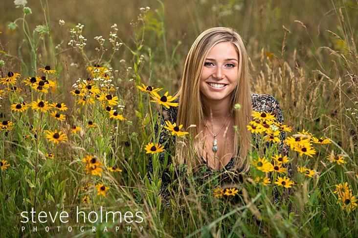 21_Blonde teen sits in field of wildflowers smiling for senior portrait.jpg