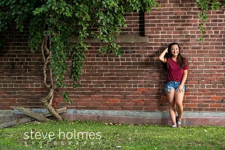 21_Teenaged girl brushes back her hair while leaning against brick wall for outdoor senior portrait.jpg