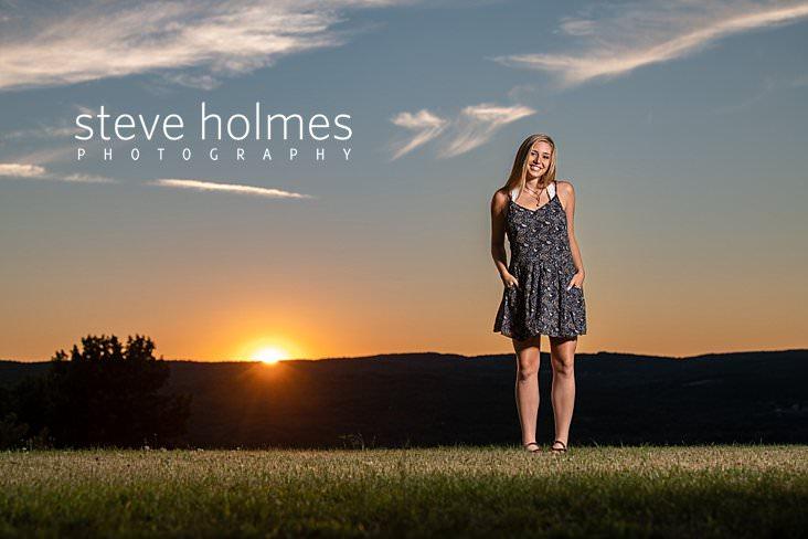 23_Blonde teen stands on hillside at sunset for senior portrait.jpg