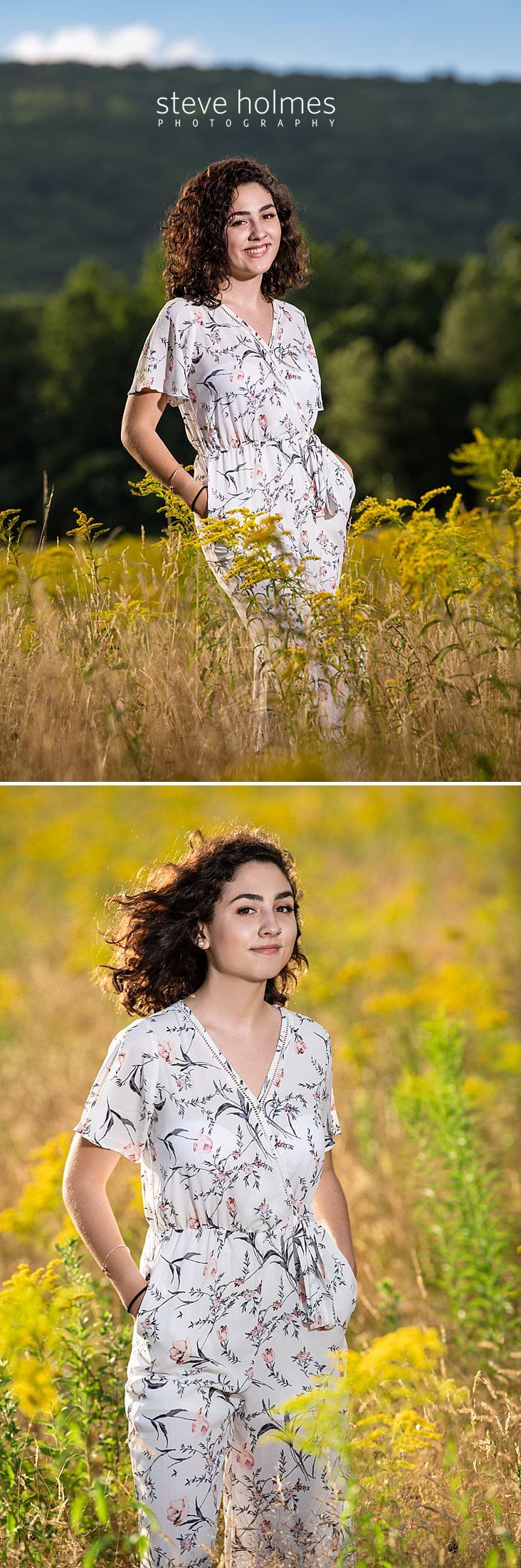 08_Curly haired brunette in jumper smiles for senior photo in New England field.jpg