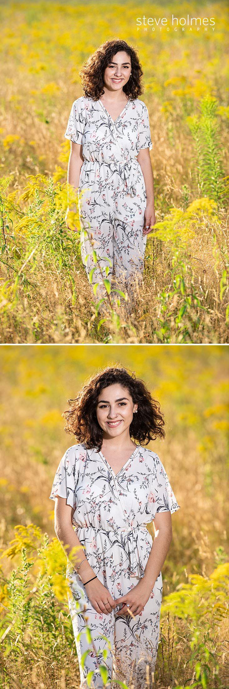10_Curly haired brunette in jumper walks in a field for senior photo.jpg